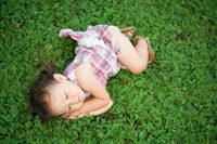 Kleines Mädchen schläft auf Wiese