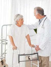 Frau mit Rollator redet mit Arzt