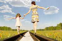 Mutter und Kind balancieren auf Gleisen