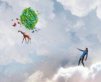 Frau in Wolken mit Luftballons