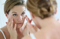 Frau betrachtet Gesichtshaut