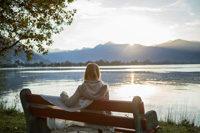 Frau auf Bank an Gebirgssee