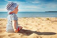 Kleinkind sitzt am sonnigen Strand