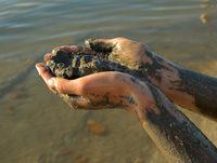 Hände halten Schlick, Meer