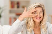 Frau schaut durch 2 gespreizte Finger