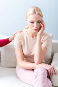 Frau auf Sofa sitzend, traurig