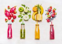 4 Trinkflaschen, darüber versch.Obst
