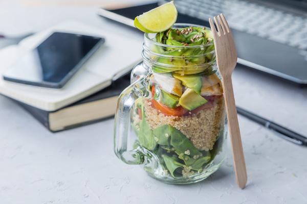 Glas mit Salat und Reis auf Schreibtisch