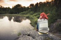 Frau sitzt am Seeufer