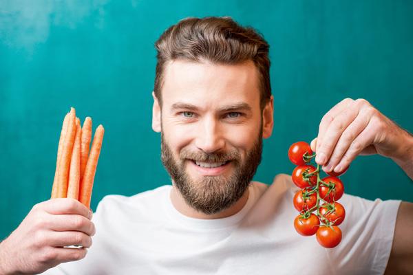 Mann mit Tomaten und Möhren