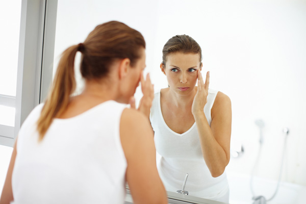 Frau betrachtet Gesicht im Spiegel