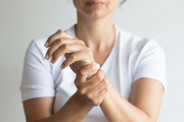 Frau umfasst linkes Handgelenk