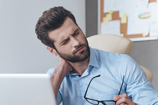 Mann Hand im Nacken, Laptop