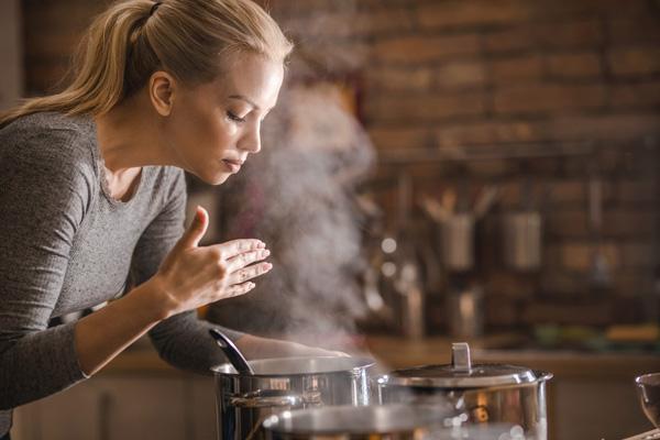 Junge Frau Geruchsprüfung am Kochtopf