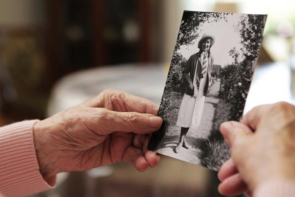 Junge und alte Hand halten s/w-Foto