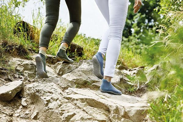 Zwei Barfußschuhträger laufen über Felsen