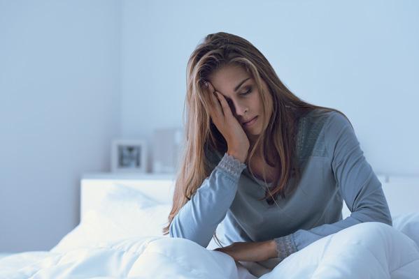 Frau im Bett sitzend stützt Kopf