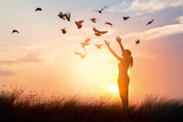 Frau im Sonnenuntergang auf Wiese, über ihr Vögel