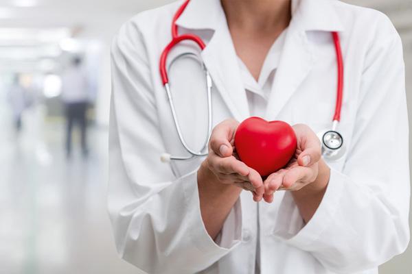 Ärztin hält rotes Herz in Händen