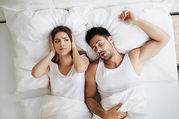 Paar im Bett, er schnarcht