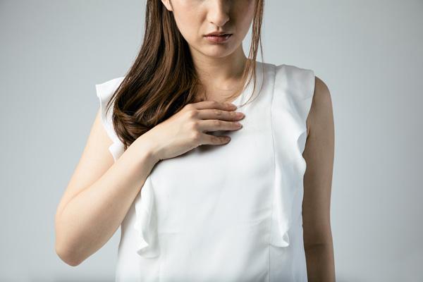 Frau in weißer Bluse hält Hand auf Brust