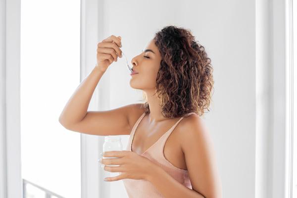 Frau, Teelöffel an Mund, Joghurtglas in der Hand
