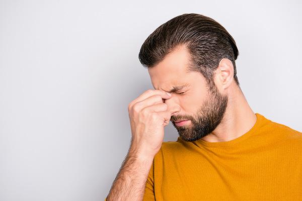 Mann Finger an Nasenwurzel